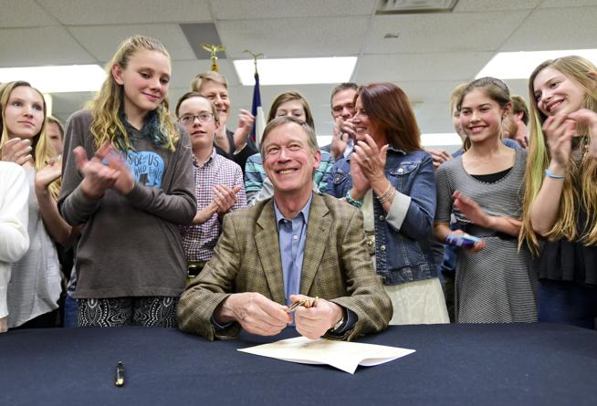 Colorado Gov. John Hickenlooper, center, smiles after signing HB16-1063 into law while surrounded by a group of students at Sunset Middle School in Longmont on Wednesday. (Matthew Jonas / Staff Photographer)